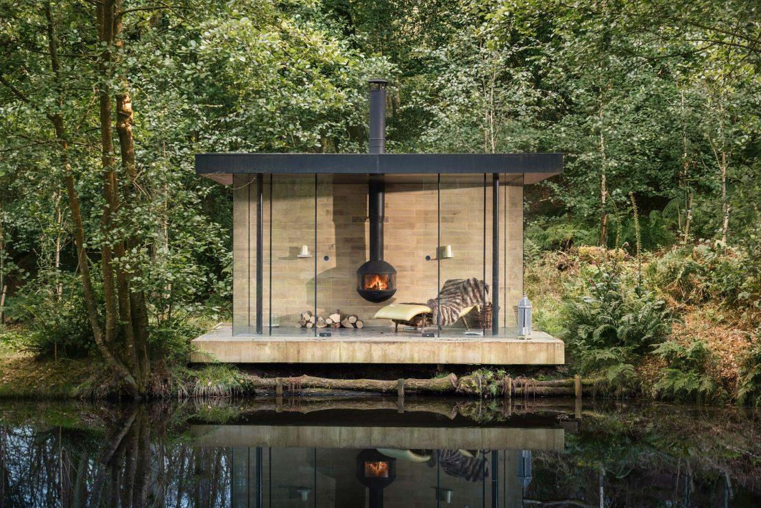 Pequeno ambiente integrado à natureza com lareira e espaço para leitura e descanso.